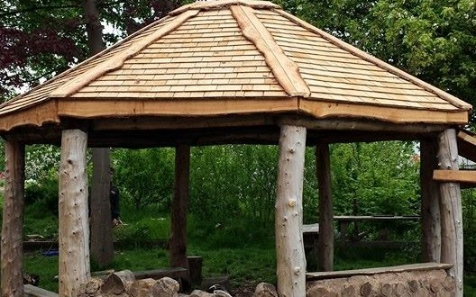 Completed shingle roof on the roundhouse looking towards the nature area. cob and cordwood walls made by the school children using the off cuts from the frame.